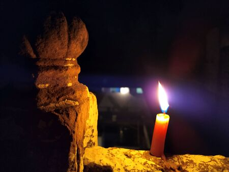 A CANDLE FLAME GIVE LIGHT IN DARK NIGHT WITH BIG STONE
