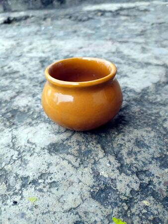 A BROWN COLOR CLAY POT PUT ON THE ROAD