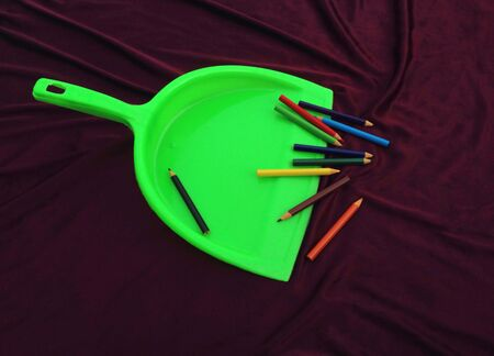 green garbage cleaner with color pencil isolated on brown background