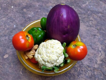 many fresh healthy vegetable put in a plastic boul on stone background