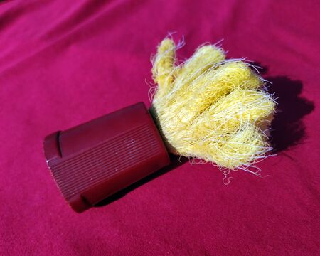 a red and yellow plastic saving brush isolated on red background