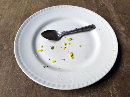 a white clay plate with some food and a spoon isolated on stone background Zdjęcie Seryjne
