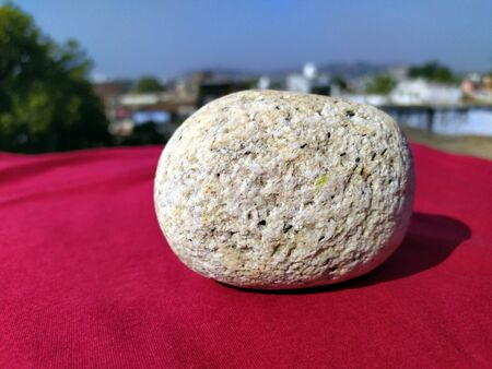 a white marbal stone put on red floor and nature background