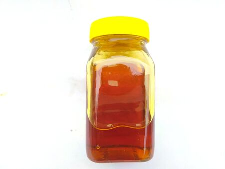 yellow color glass bottle in honey put in the bottle isolated on white background