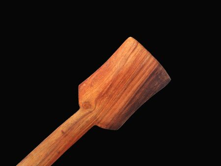 a wooden spatula isolated on black background
