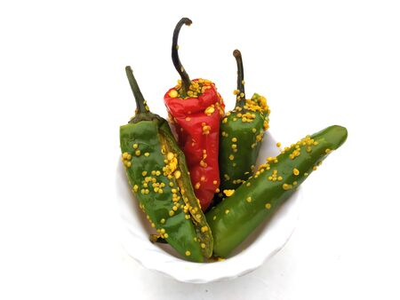 fresh green and red  chilli pickle put in a  bowl isolated on white