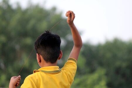 a children is trying to flying a kite but their kite is not flying