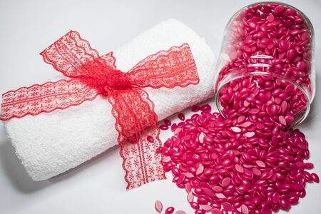 on a white background is a red granular wax in a glass jar and a white towel with a red bow. 스톡 콘텐츠 - 132488268
