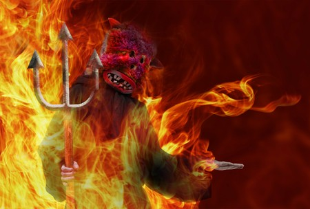 fire show: Man dressed as a devil with a trident Stock Photo