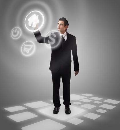 technology symbols metaphors: Business man choosing home button, futuristic digital technology Stock Photo