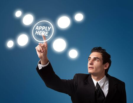 find a job: Business man pressing a Apply HERE button.  Stock Photo