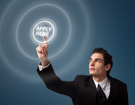 search button: Business man pressing a Apply HERE button.  Stock Photo