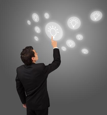 pressing: business man pressing lightbulp button  Stock Photo