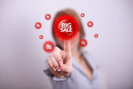 Woman pressing modern big sale button with one hand photo