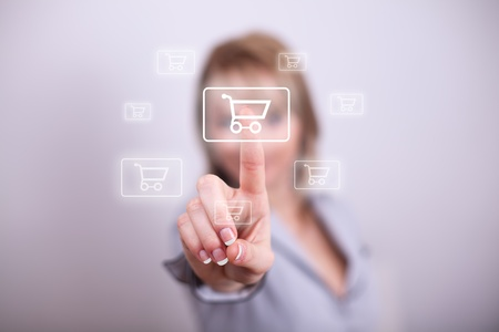 Woman pressing modern shopping cart button with one hand photo