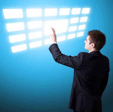 Young business man pressing a touchscreen button Stock Photo - 9114600