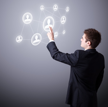 Young business man pressing a digital social network icon. Stock Photo - 9213727