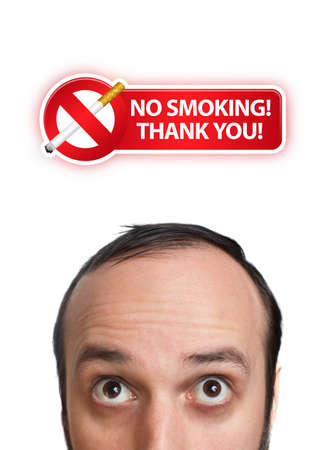 Young man with NO SMOKING sign over his head 2, isolated on white background  photo