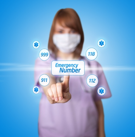 emergency number: woman doctor pressing digital button ( Emergency Number ) Stock Photo