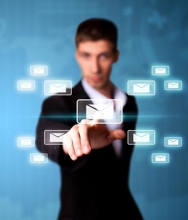 Man pressing email icon, futuristic technology Stock Photo - 9342339