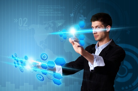touch screen interface: Man pressing modern touch screen buttons with a blue technology background Stock Photo