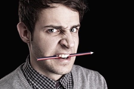 portrait of a young angry man with pencil  photo