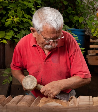 Old woodcarver working with mallet and chisel 10 photo