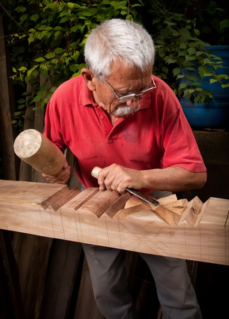 Old woodcarver working with mallet and chisel 9 photo