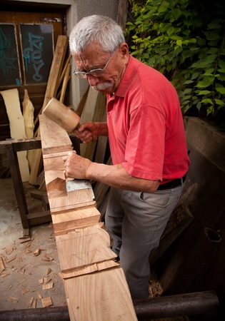 Old woodcarver working with mallet and chisel 4 photo