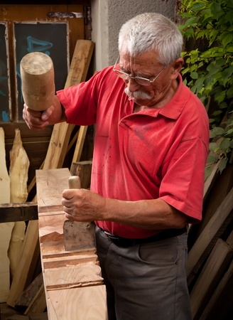 Old woodcarver working with mallet and chisel 2 photo
