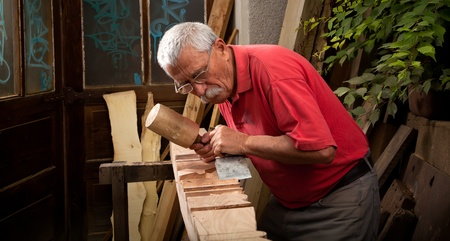 Old woodcarver working with mallet and chisel photo