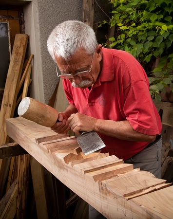Old woodcarver working with mallet and chisel 8 photo