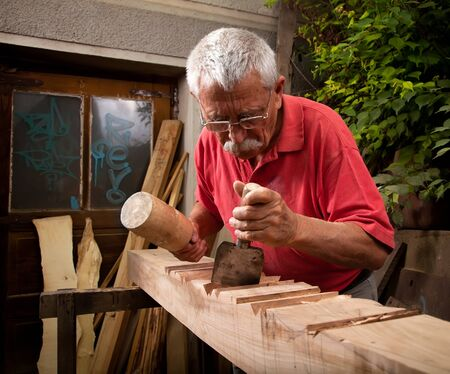 Old woodcarver working with mallet and chisel 5 photo