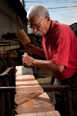Old woodcarver working with mallet and chiesel photo