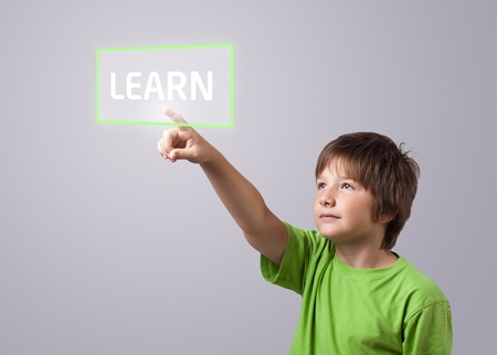 Kid touching LEARN button on a touchscreen  photo