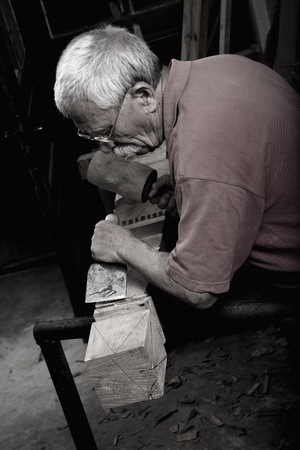Old woodcarver working with mallet and chiesel Stock Photo - 10283371