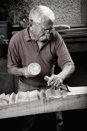 Old woodcarver working with mallet and chiesel, vintage style photo