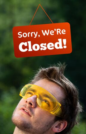 Young persons head looking at closed and open signs Stock Photo