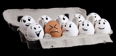 The odd one, funny eggs with smiley faces photo