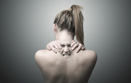 woman back of head: A nude back of a woman indicating neck pain  Stock Photo
