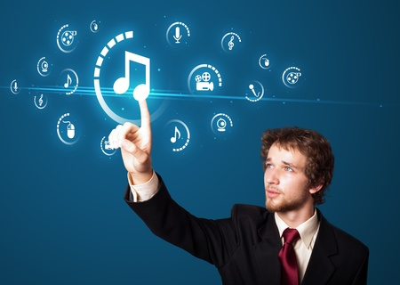 digital music: Businessman pressing multimedia type of modern buttons with virtual background Stock Photo