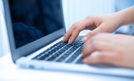 Close-up of typing female hands photo