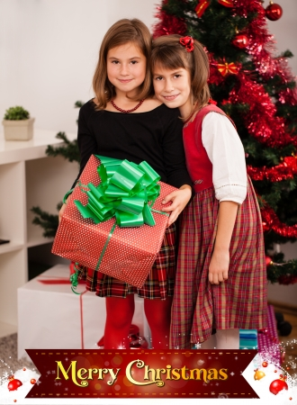 Kids with their christmas presents with Merry Christmas sign photo