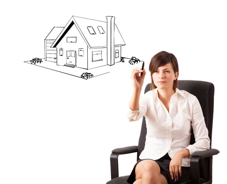 Young woman drawing a house on whiteboard isolated on white photo