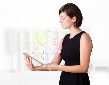 Young business woman looking at modern tablet with currency icons photo