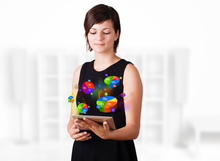 Young business woman looking at modern tablet with colourful pie charts Stock Photo - 16242646