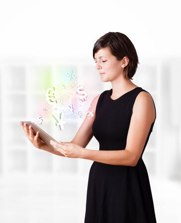 won: Young business woman looking at modern tablet with currency icons