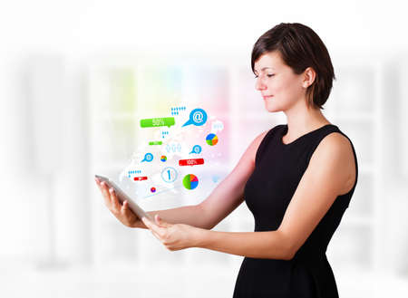 Young business woman looking at modern tablet with colourful technology icons Stock Photo - 16242953