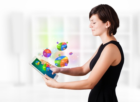 Young business woman looking at modern tablet with colourful pie charts Stock Photo - 16243046