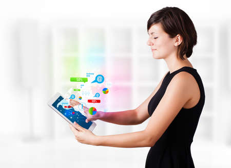 Young business woman looking at modern tablet with colourful technology icons Stock Photo - 16243010